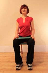 sitting with stretch-band around thighs, opening legs to work against band