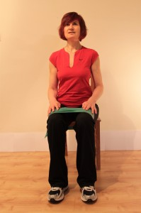 sitting with stretch-band around thighs at start of hip-wrap