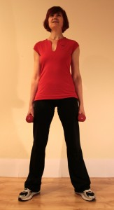 Standing, legs wide, dumbell in each hand at start of exercise