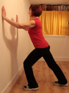 Standing leaning on wall with one leg lengthened behind for calf stretchh