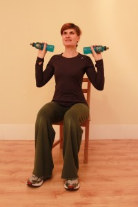 Sitting with arms bent at sides holding bottles, ready to raise arms