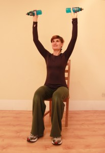 Sitting with arms raised high, holding bottles, for arm-raise exercise
