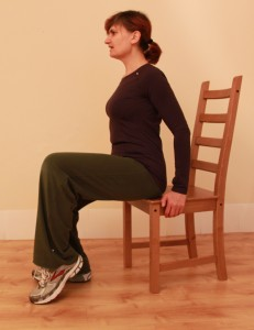 Sitting with pointed foot as part of ankle loosening exercise