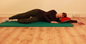 Lying on side with bottom knee drawn in towards chest, top leg long, for start of exercise