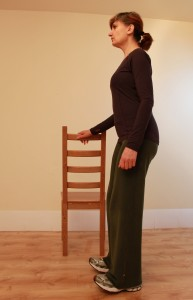 Standing side-on to a chair-back with one hand on it for balance support, pulling up toes