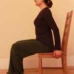 Sitting upright in a kitchen chair, hands lightly supporting at the sides of the chair
